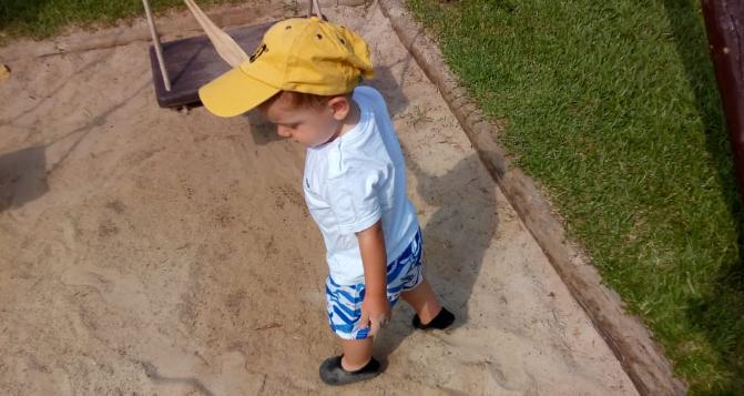 Foto de um menino de boné amarelo brincando num parquinho.