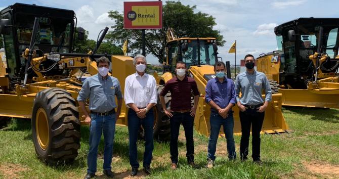 Fotografia de quatro homens adultos usando mascaras em frente a equipamentos Cat®