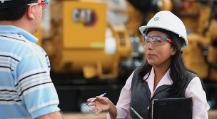Fotografia de um homem  dialogando com uma mulher em frente a um equipamento CAT®